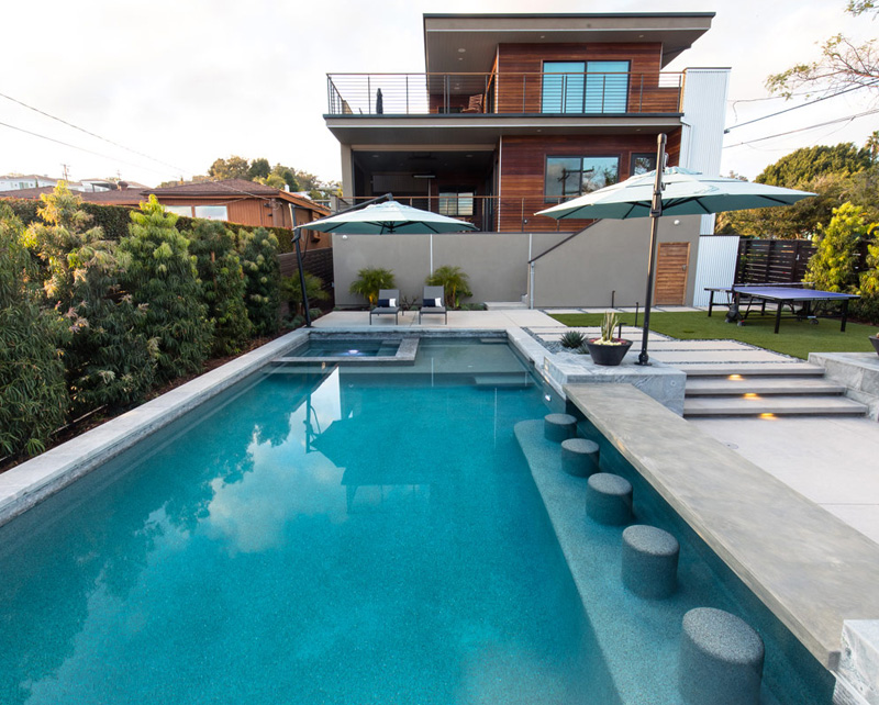 A custom linear pool with a jacuzzi and umbrellas