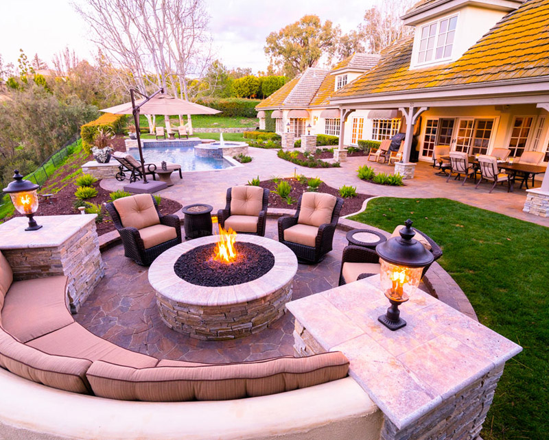 A custom pool surrounded by landscaping and a beautiful fire pit.
