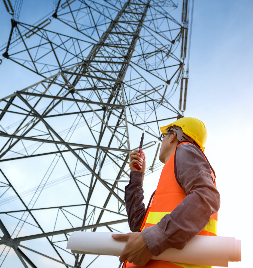 Worker with walky talky reviewing hydro tower