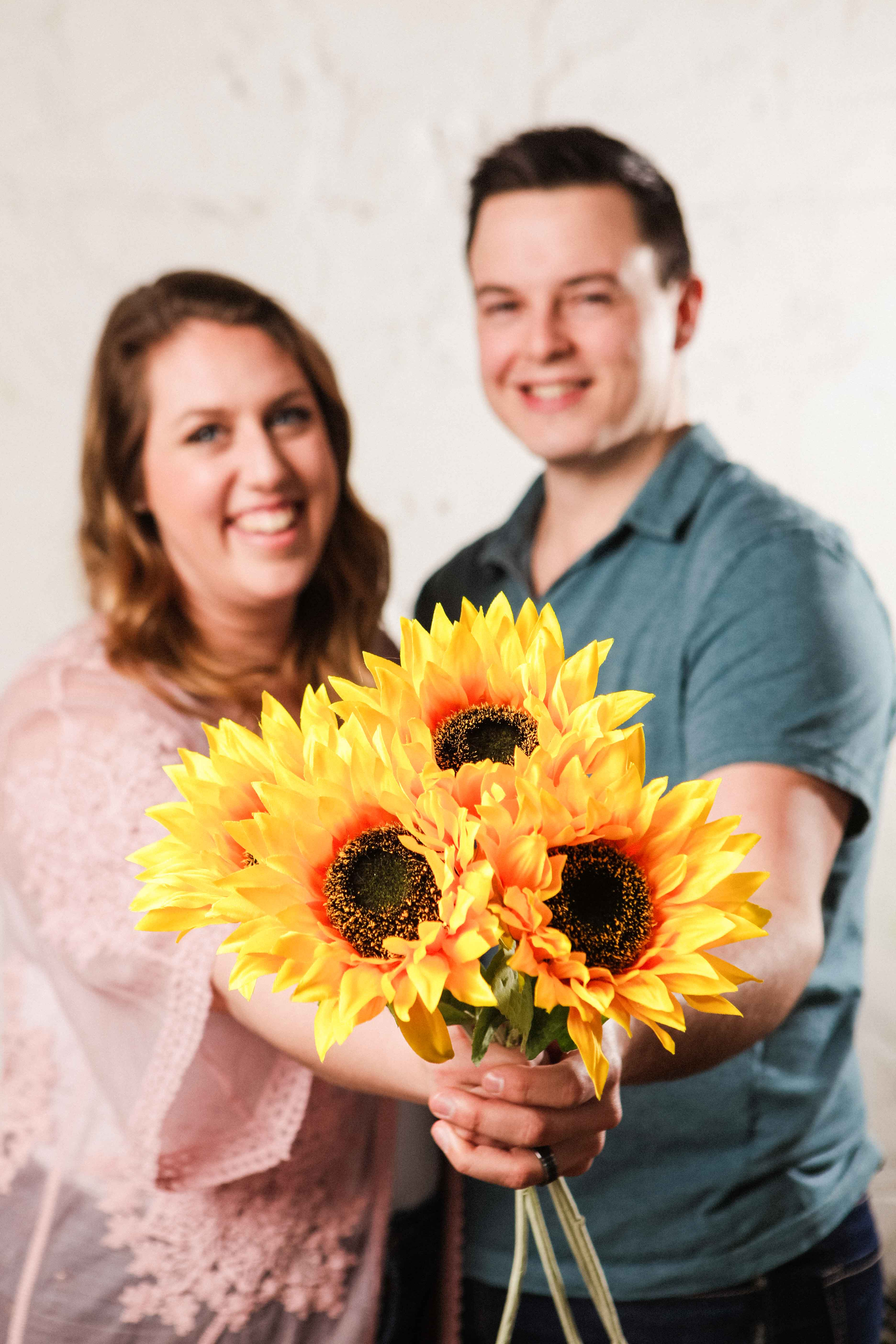 Photo of Stephanie and Jakob from Fields of Gold holding a bundle of sunflowers