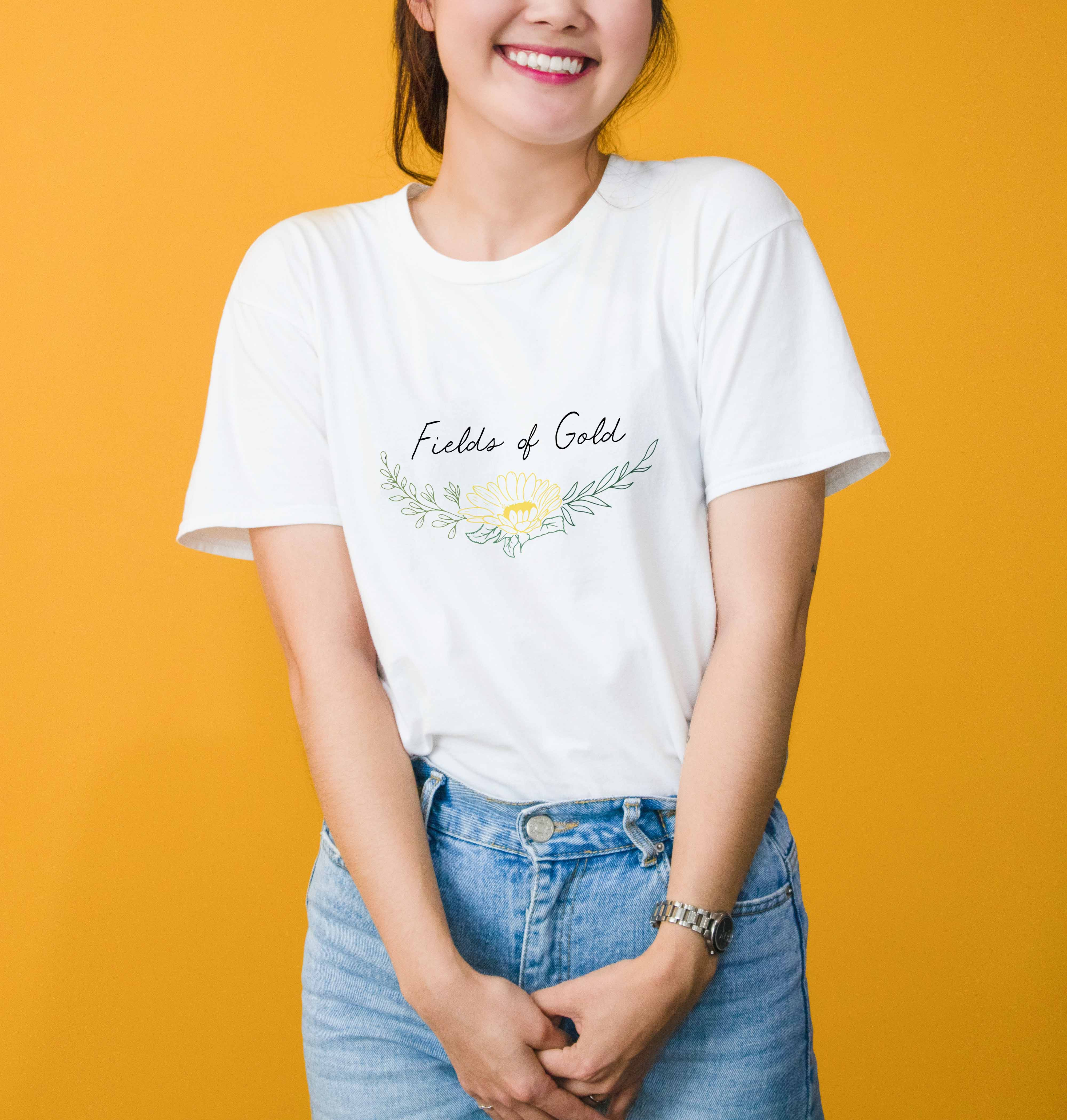 Photo of person wearing a white t-shirt with the Fields of Gold logo on it