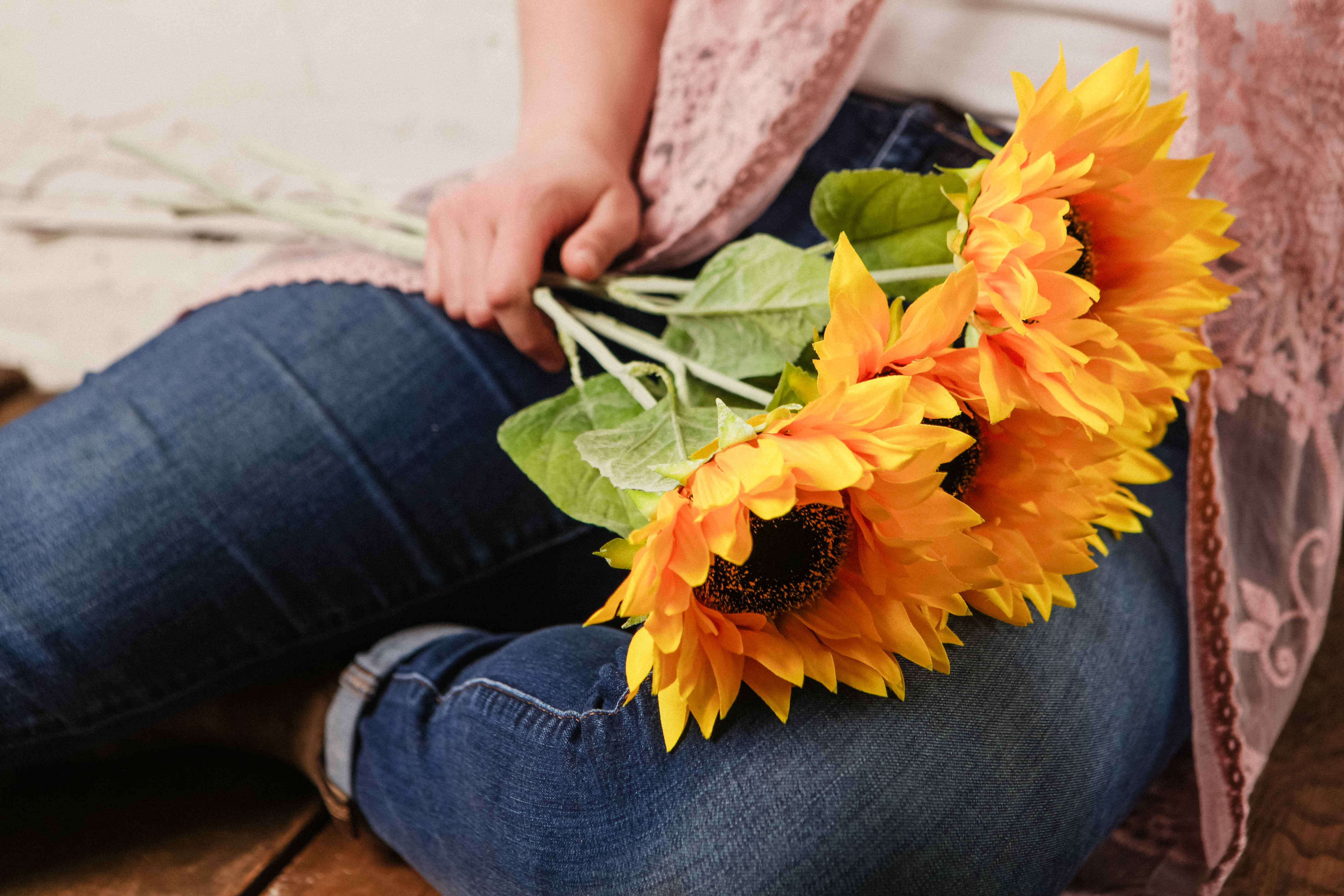 Bundle of flowers laying on the lap of a person