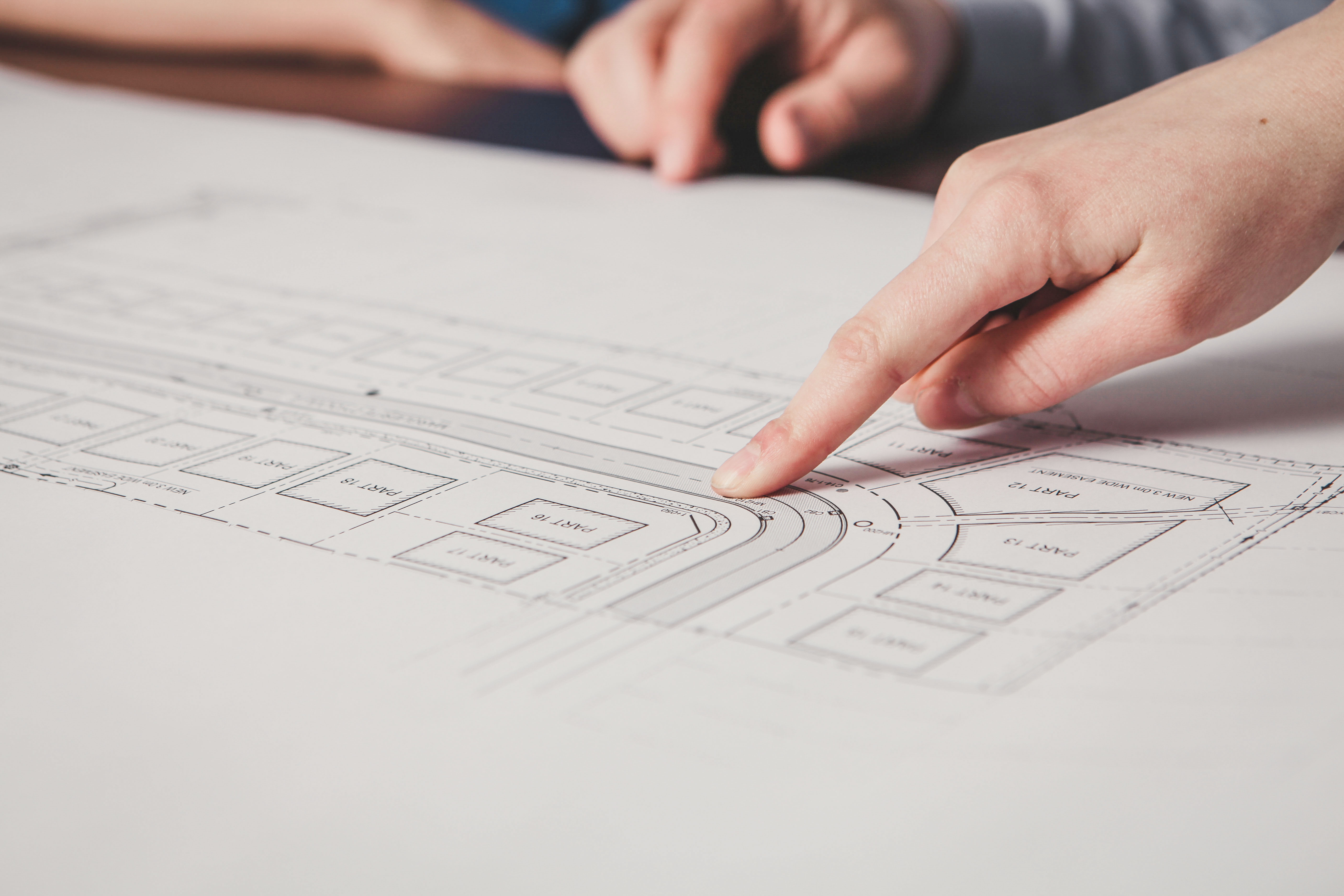 Close-up of finger pointing at Engineering plans