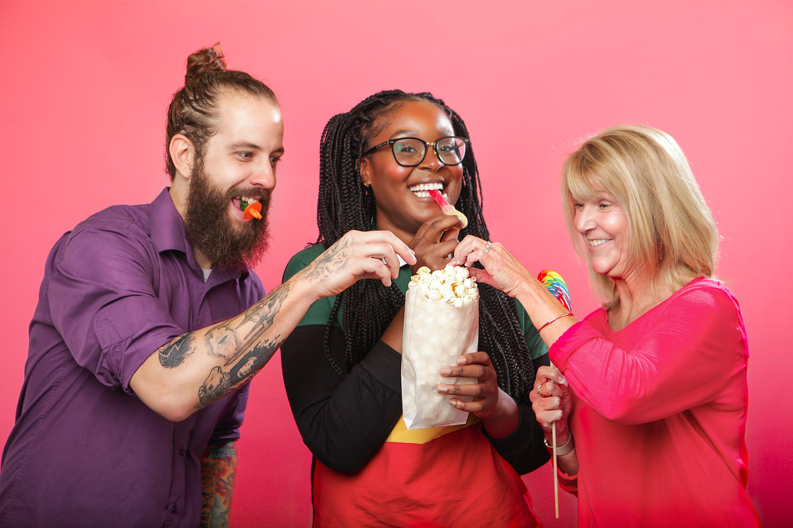 Three people enjoying candy and a bag of popcorn together