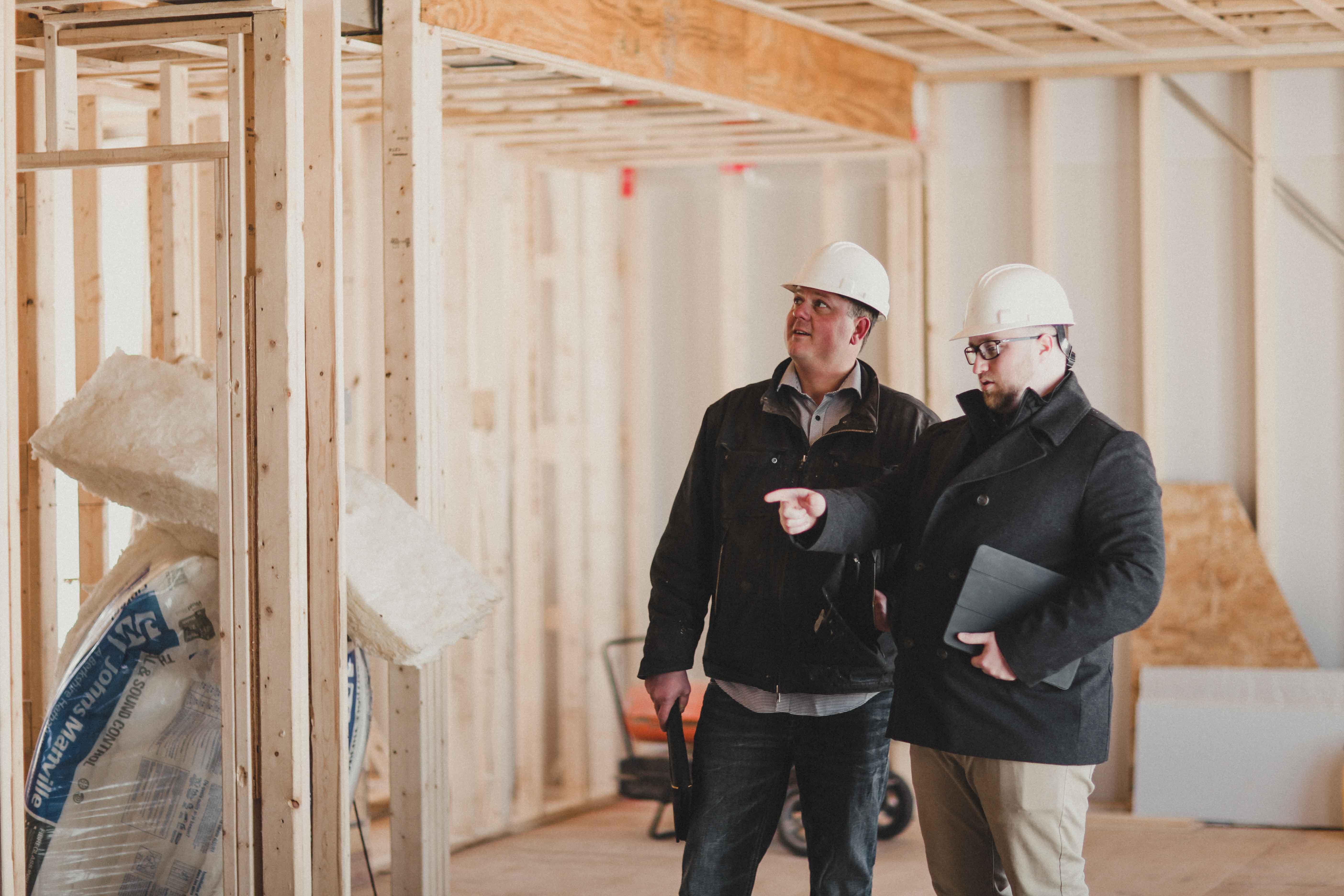 Pat Menard & Brad Robertson inspecting a house frame