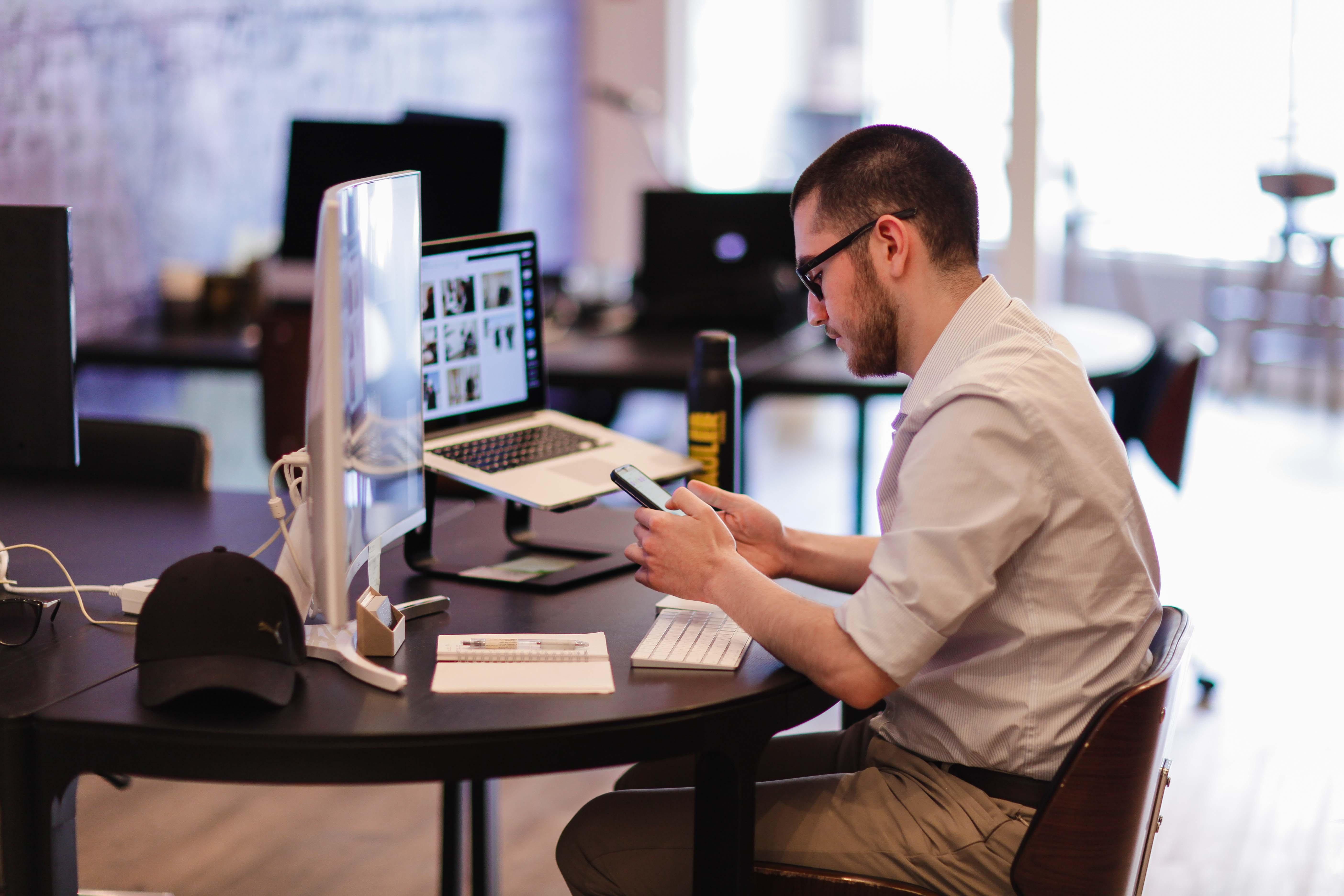Man sitting at desk using phone