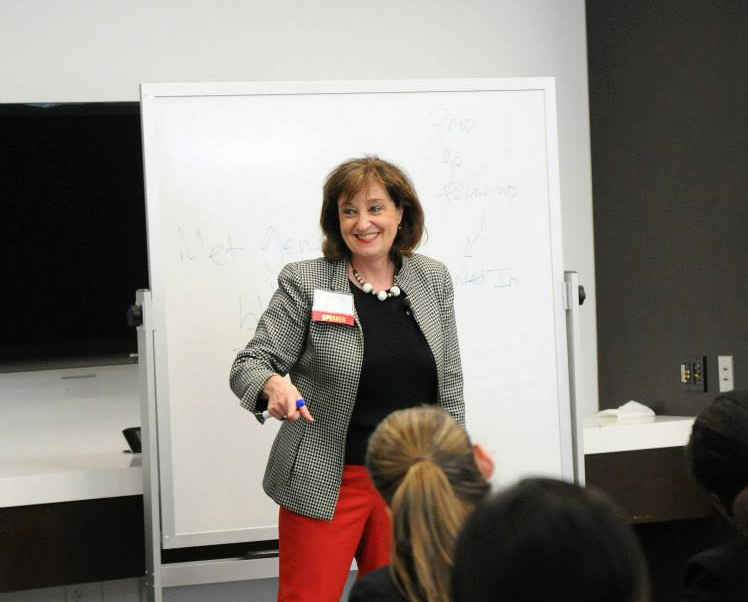 A photo of Diane in front of a whiteboard, while instructing.