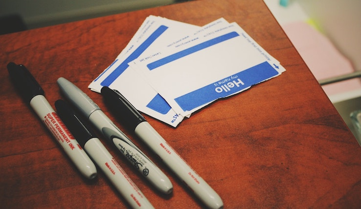 Image of blank name tags and Sharpie markers.