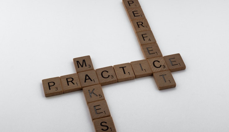 """Image of a pieces from the game scrabble that spell """"practice makes perfect"""""""