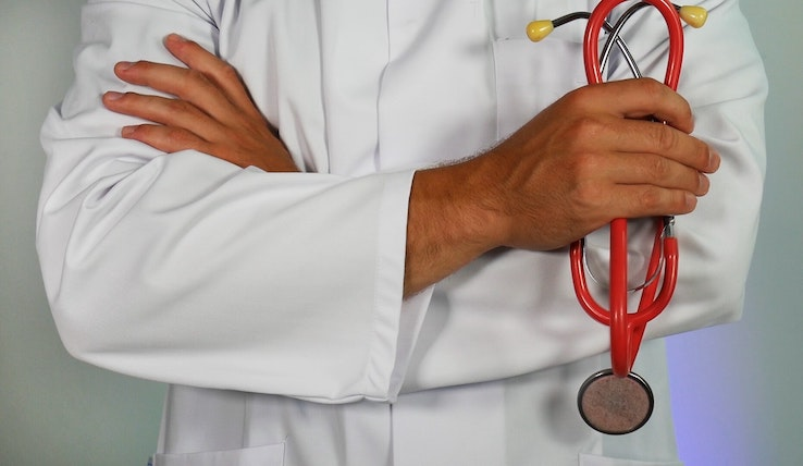 Image of the torso of a doctor in a white coat with a red stethoscope.