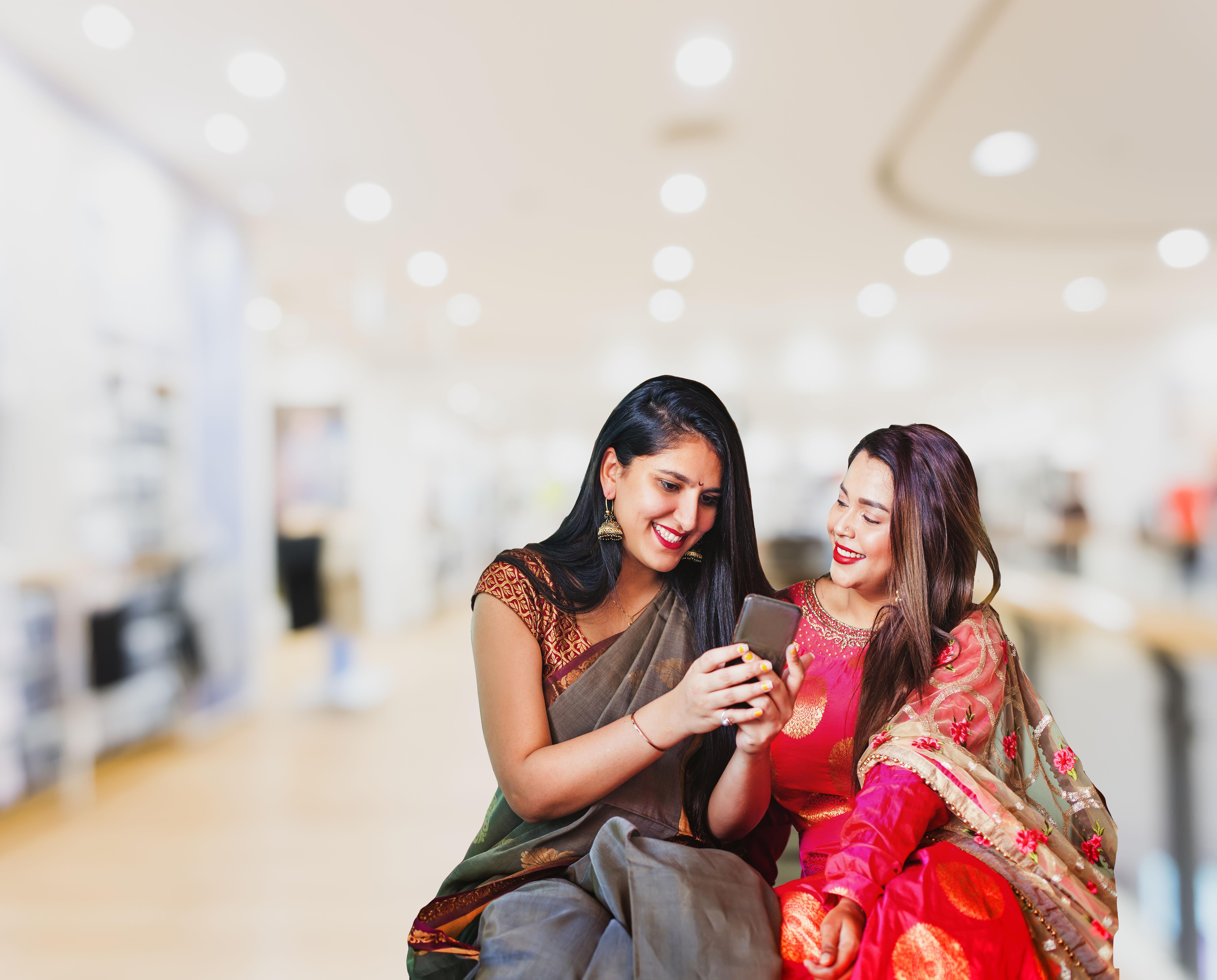 Two indian women using phone Sheores money