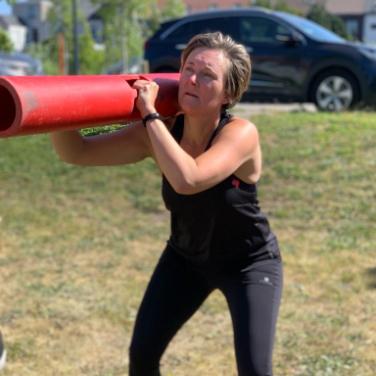 Foto van katrien in sportkledij met een rode buis op haar schouder, midden een oefening