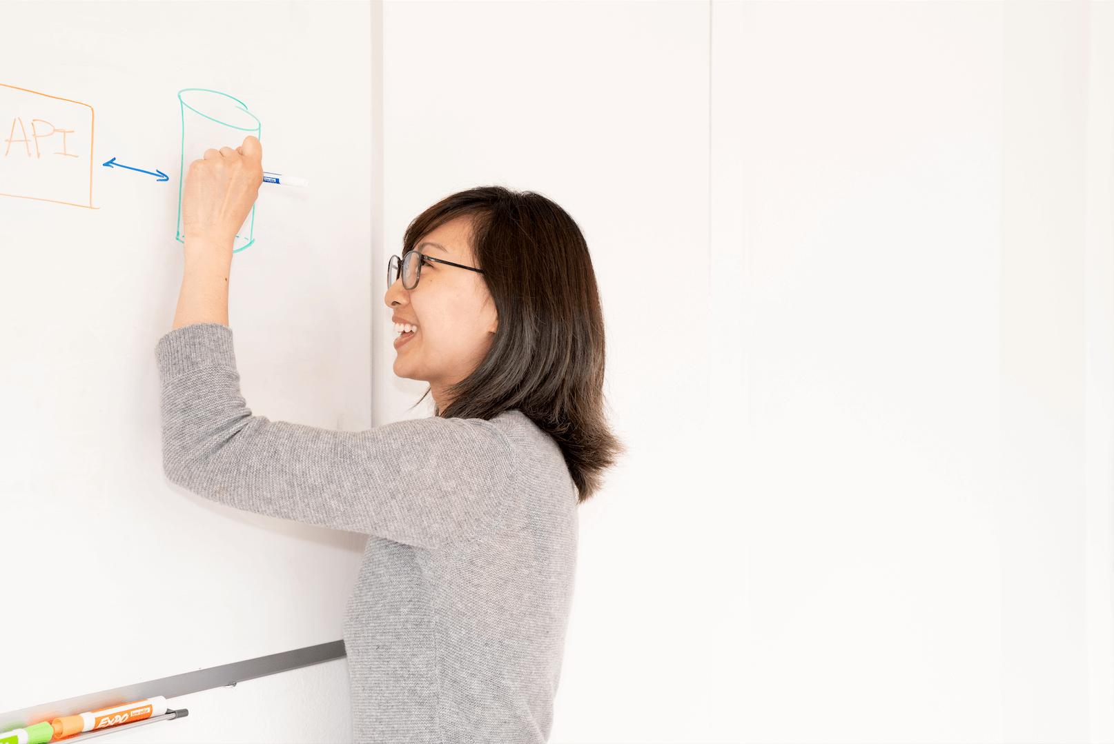 Woman draws on whiteboard