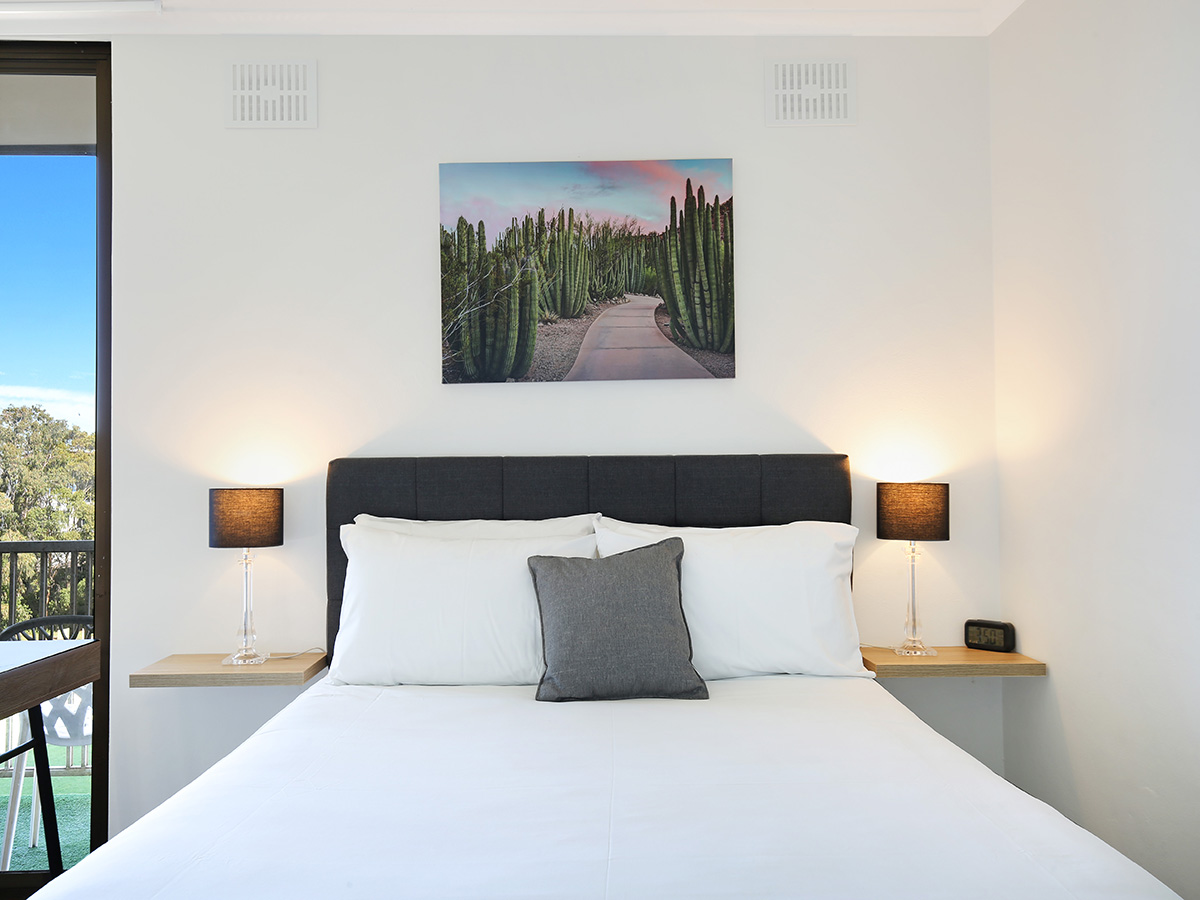 A queen bed with two bed side tables either side. With a picture of cactus' hanging above.