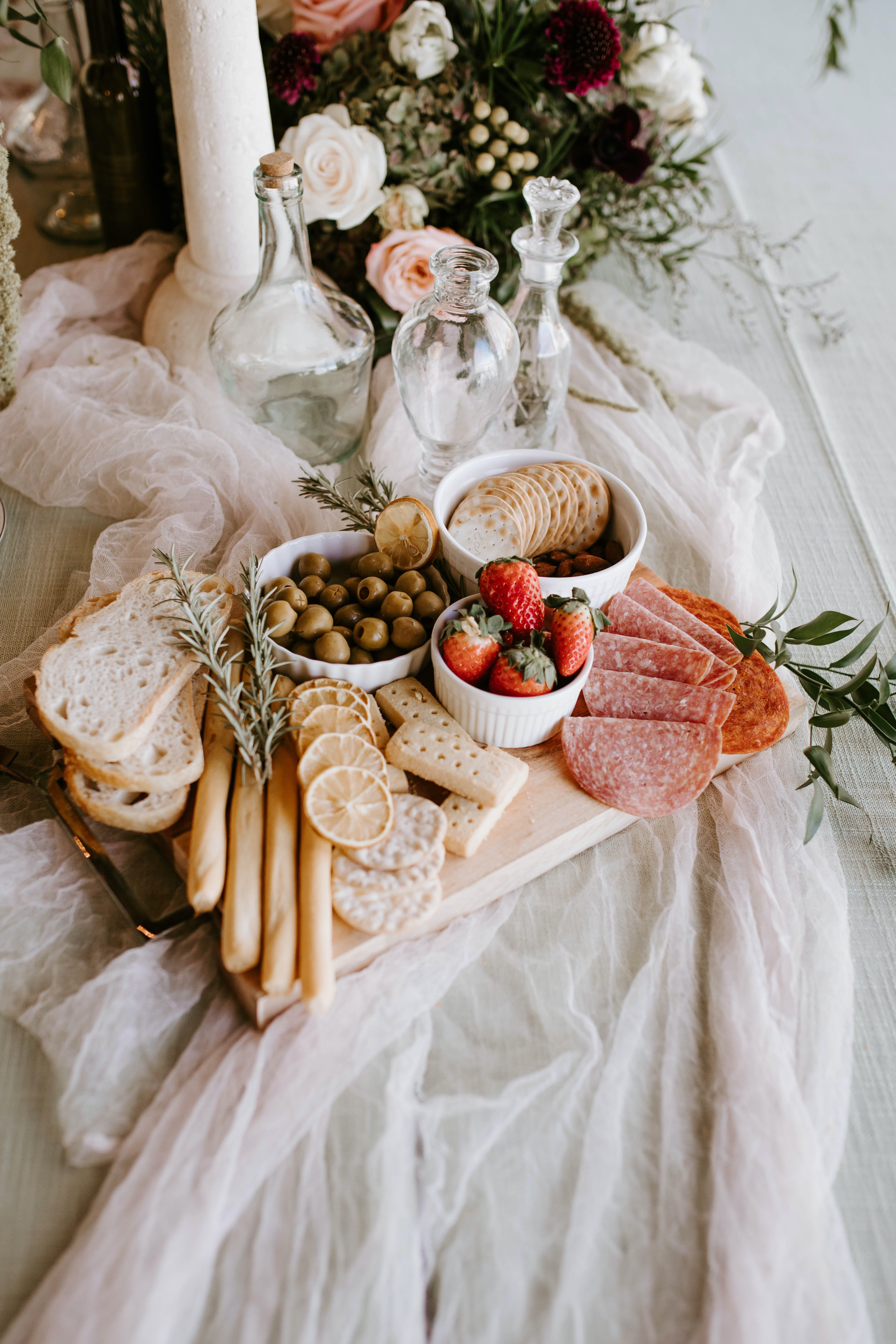 A platter of crackers, meats, cheeses, breads, fruits, nuts and meats.
