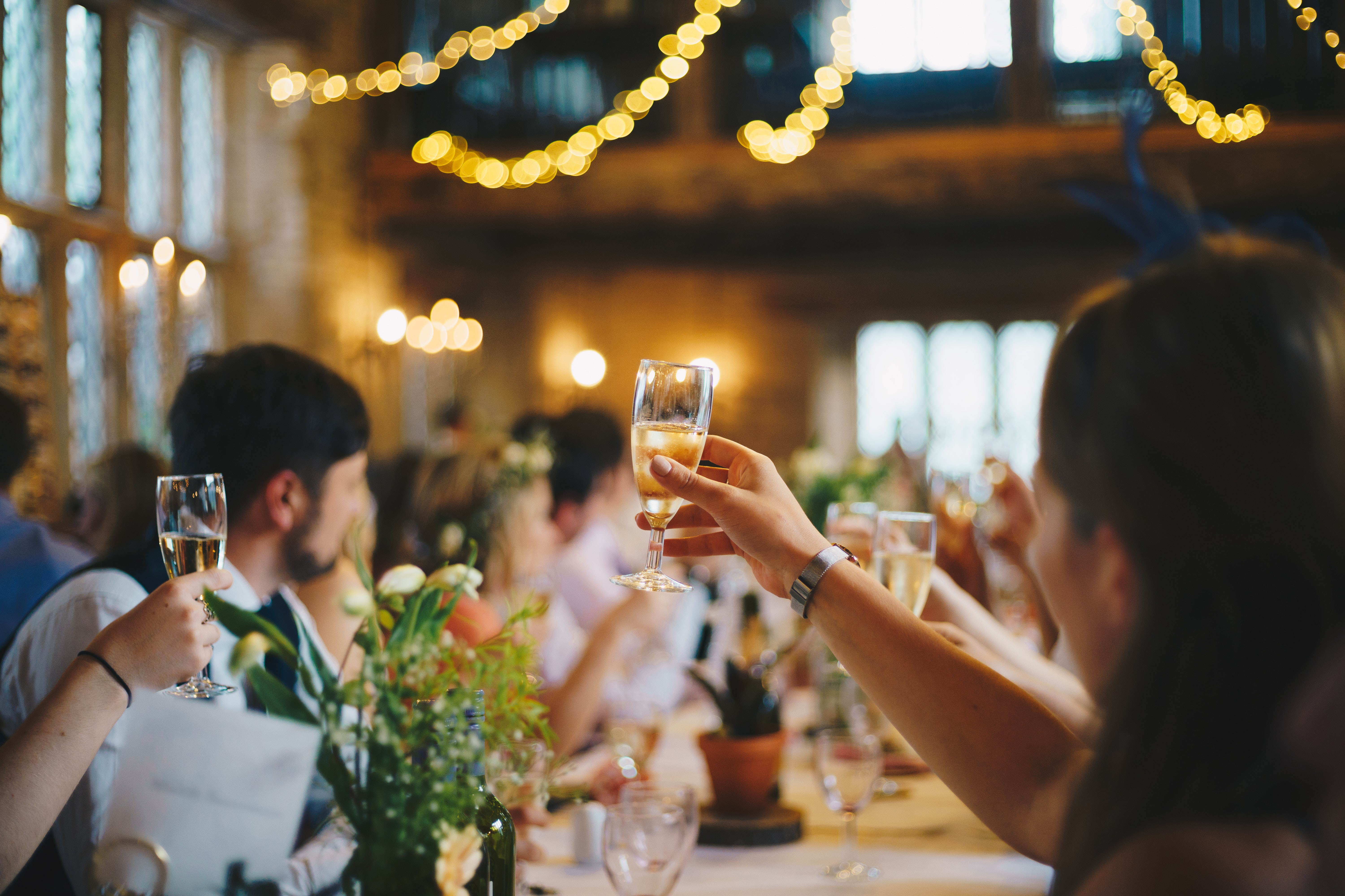 A wedding reception. People sitting around a table in the foreground. One raising a champagne glass for a toast.
