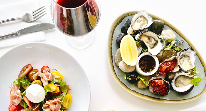 W top down shot of a dish of oysters, a glass of red wine and a tomato and pancetta salad.