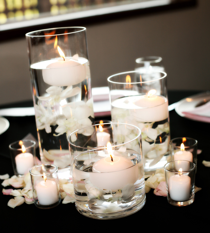 Three large vases with filled with water. A candle floating in each with white petals.