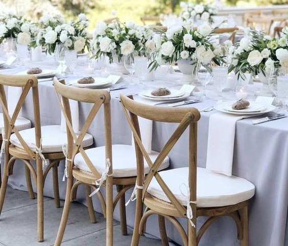 A nicely set table with three chairs, white flowers along the middle of the table and place settings laid out nicely.