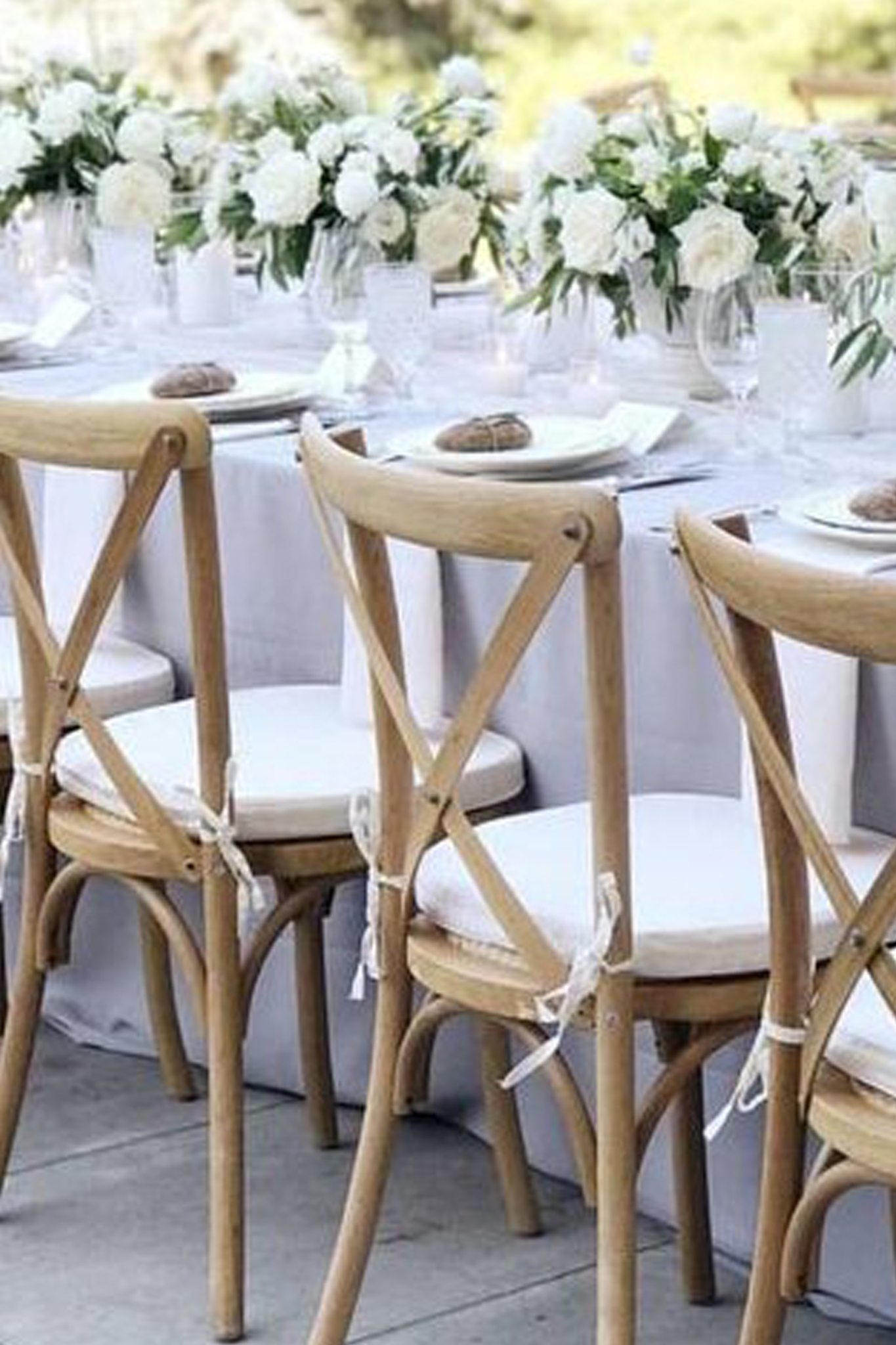 A table setting with three chairs, white flowers and place settings