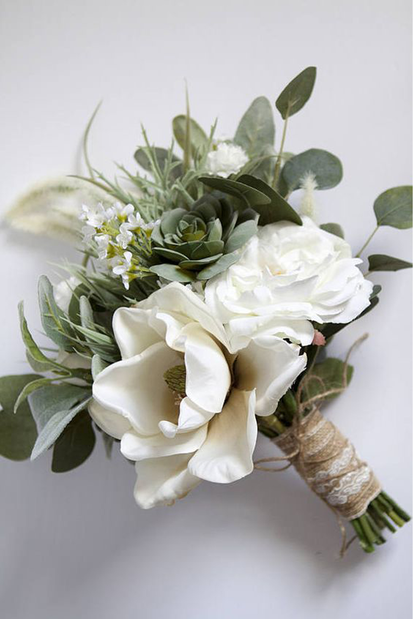 A bouquet of white roses and eucalyptus leaves wrapped in rustic twine and ribbon.