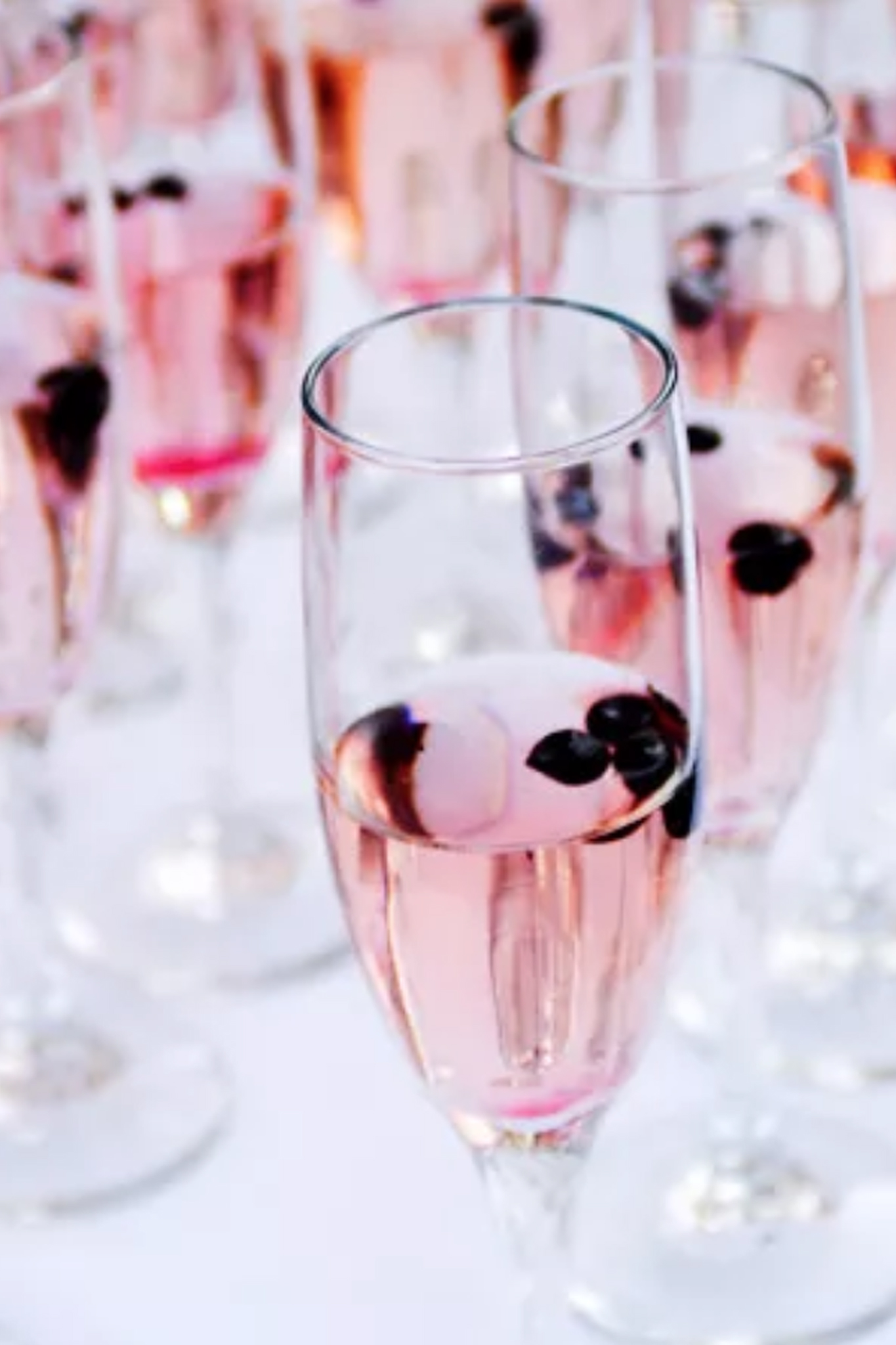 Champagne glasses in a row filled with pink champagne and berries.