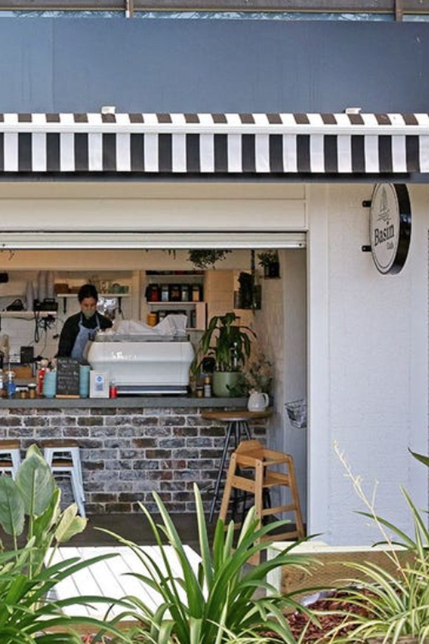 The shop front of the Basin Cafe Wollongong. A man behind a coffee machine, plants in the foreground.