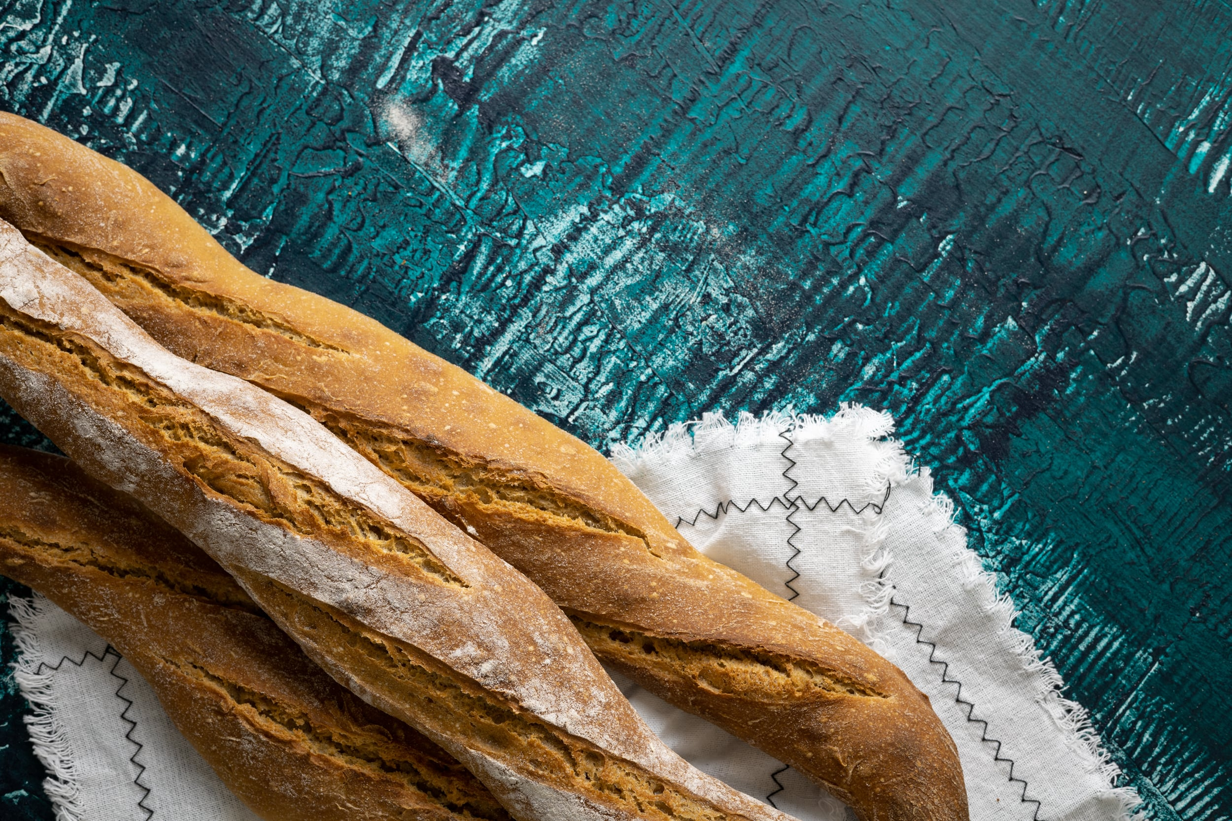 A few baguettes and a white cloth on a blue-green background
