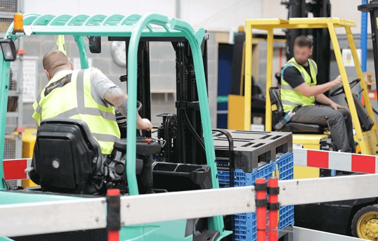 This image was taken inside of our training centre in our warehouse. Two forklift training courses can be seen being completed, one man on a green Mitsubishi Counterbalance and the another on a Yellow Hyster. Both forklifts are being driven through a chicane made out of barriers.
