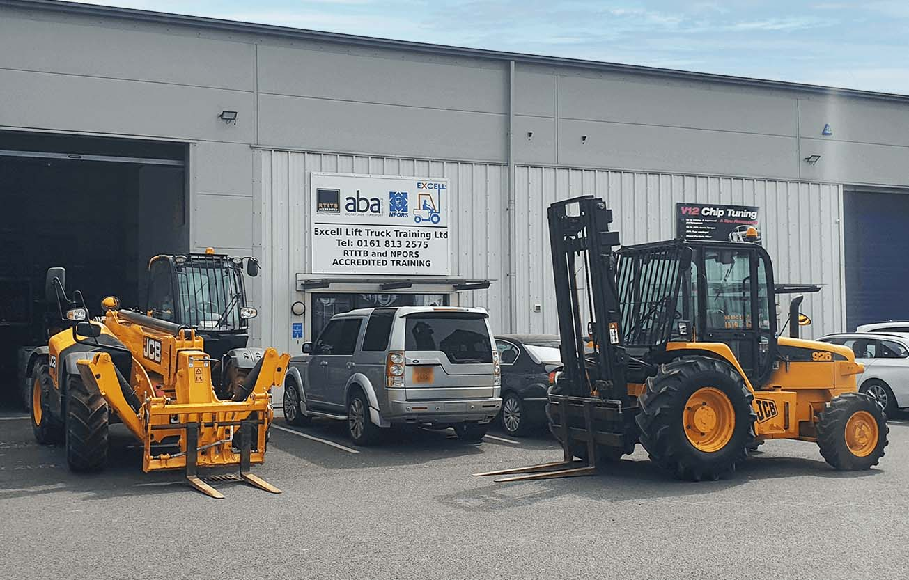 This is a picture of our forklift training centre from the outside, looking at the front of the building. There is a Rough Terrain Telescopic Handler Forklift in front of the building with a open shutter door behind it. On the right side of the image  there is a parked up Rough Terrain Masted Forklift.