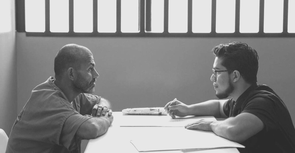 Advocate and client sitting together in jail at a table discussing their case