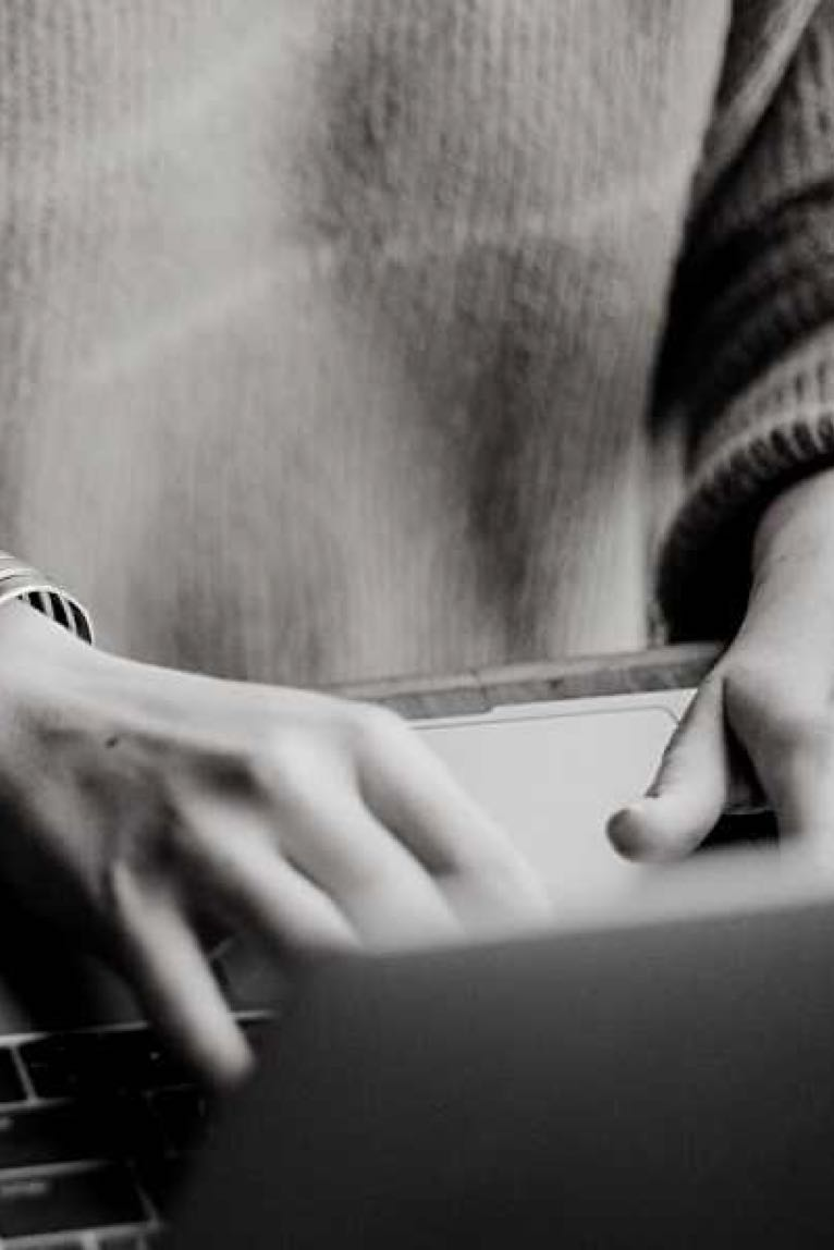 Close up of a woman's hands typing on a computer in black and white