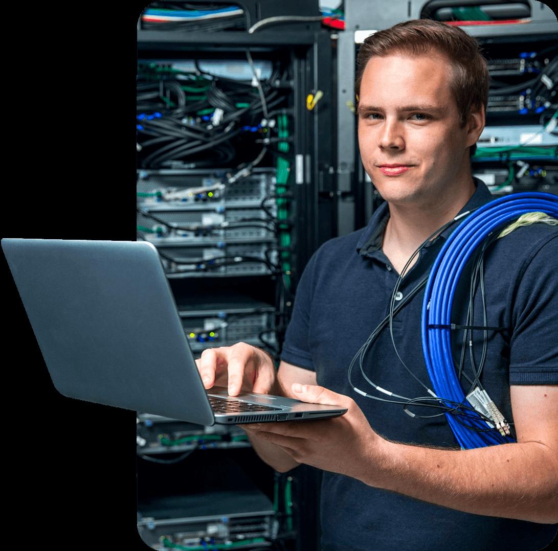 Młody mężczyzna z laptopem w pomieszczeniu serwerowni.