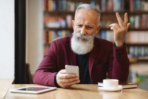 An eldery man annoyed while using a phone.