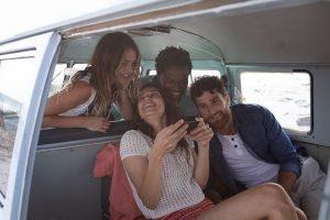 A group of people smiling while using interactive content on a phone.