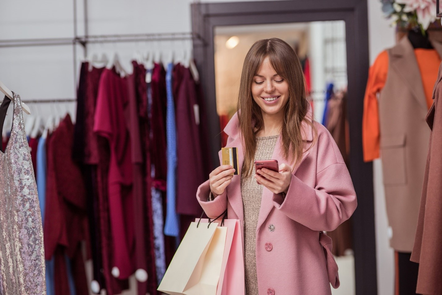 A customer smiling after receiving an SMS, representing one of the Best ecommerce trends for 2021