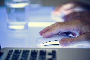 A person using a mouse to interact with online content.