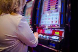 A woman using a slot machine in a casino.