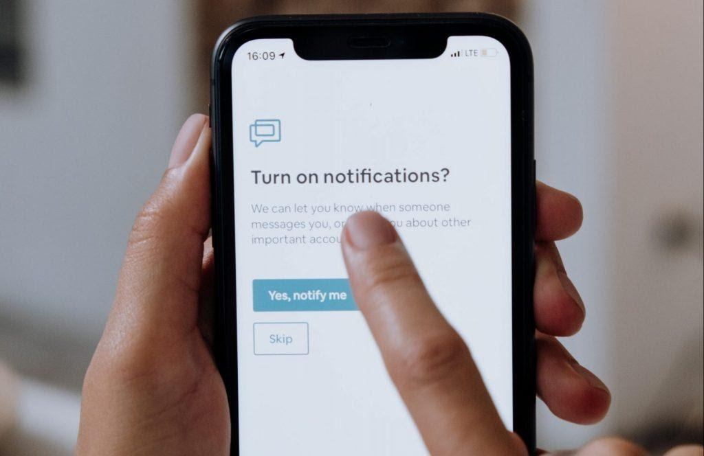 A person setting up notifications on their phone.