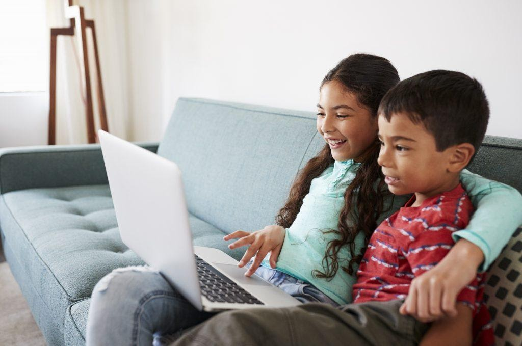 Kids smiling while looking at a laptop, showing a key aspect to keep in mind when considering user attention span in 2021.