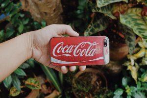 A girl holding a phone wtih a Coca-cola logo.