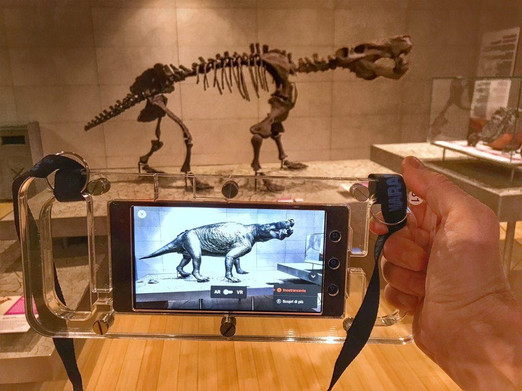 A person using an AR program on their phone to view a museum exibit.