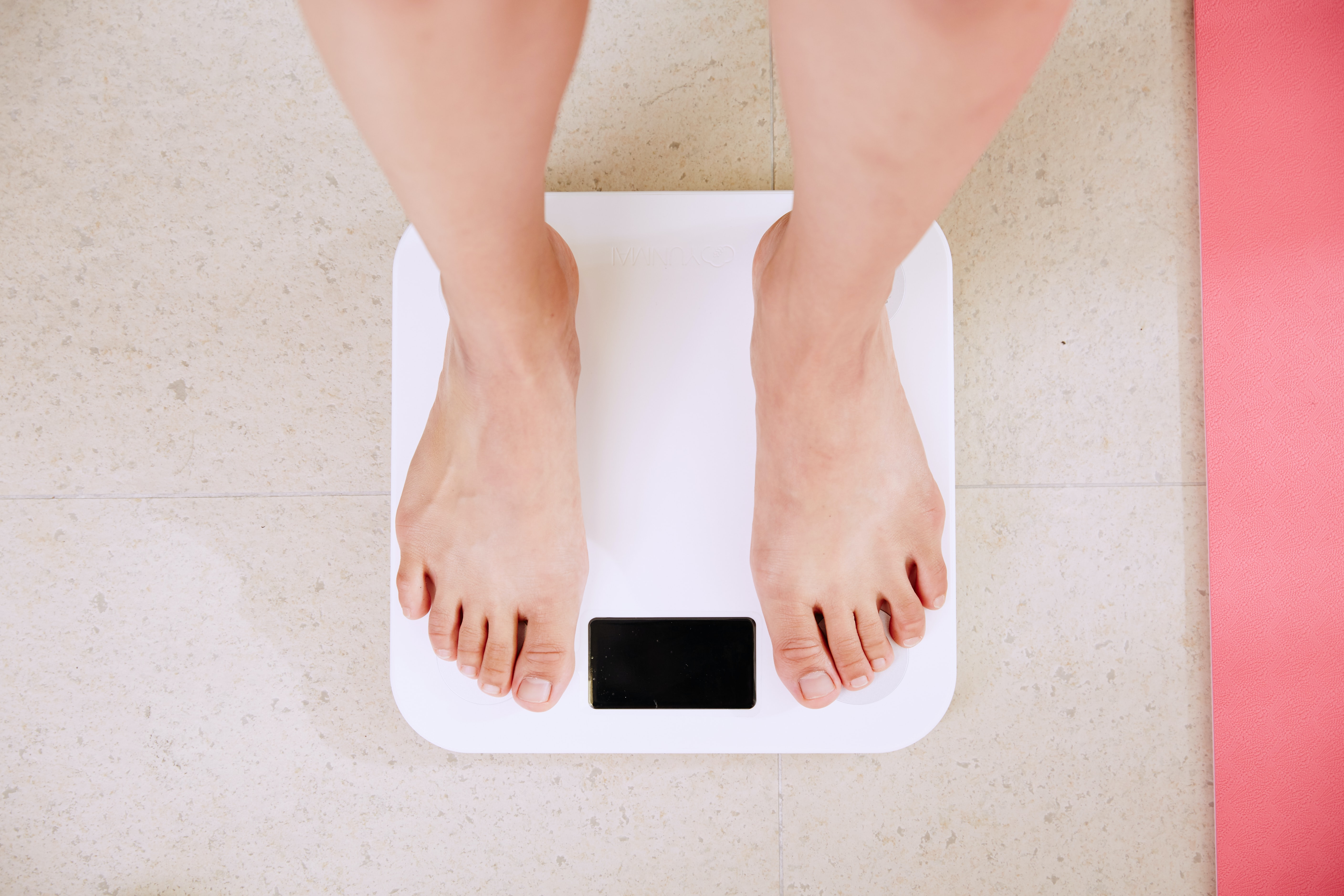 Person standing on a bathroom scale.