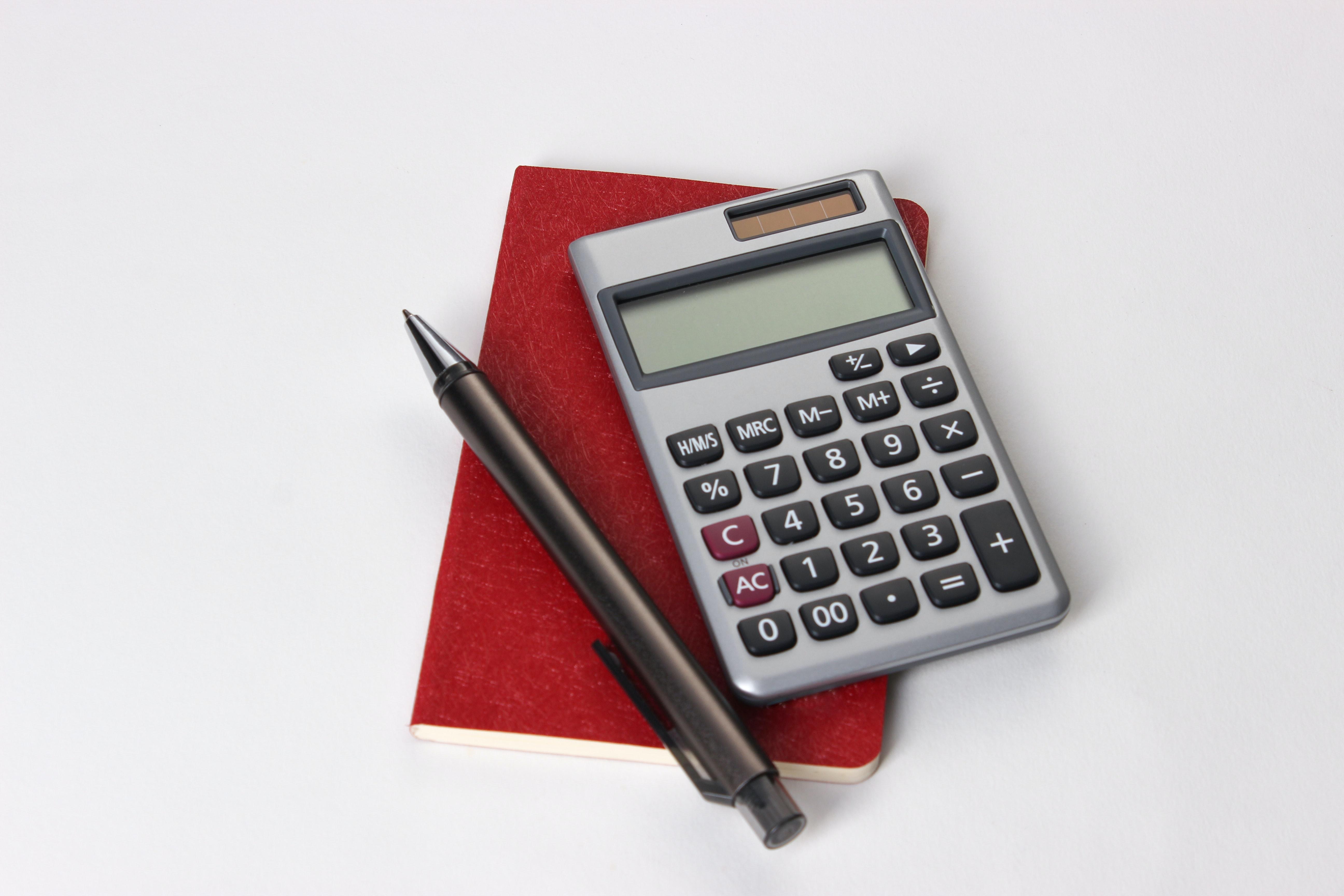 A calculator, a red note book and a pen.