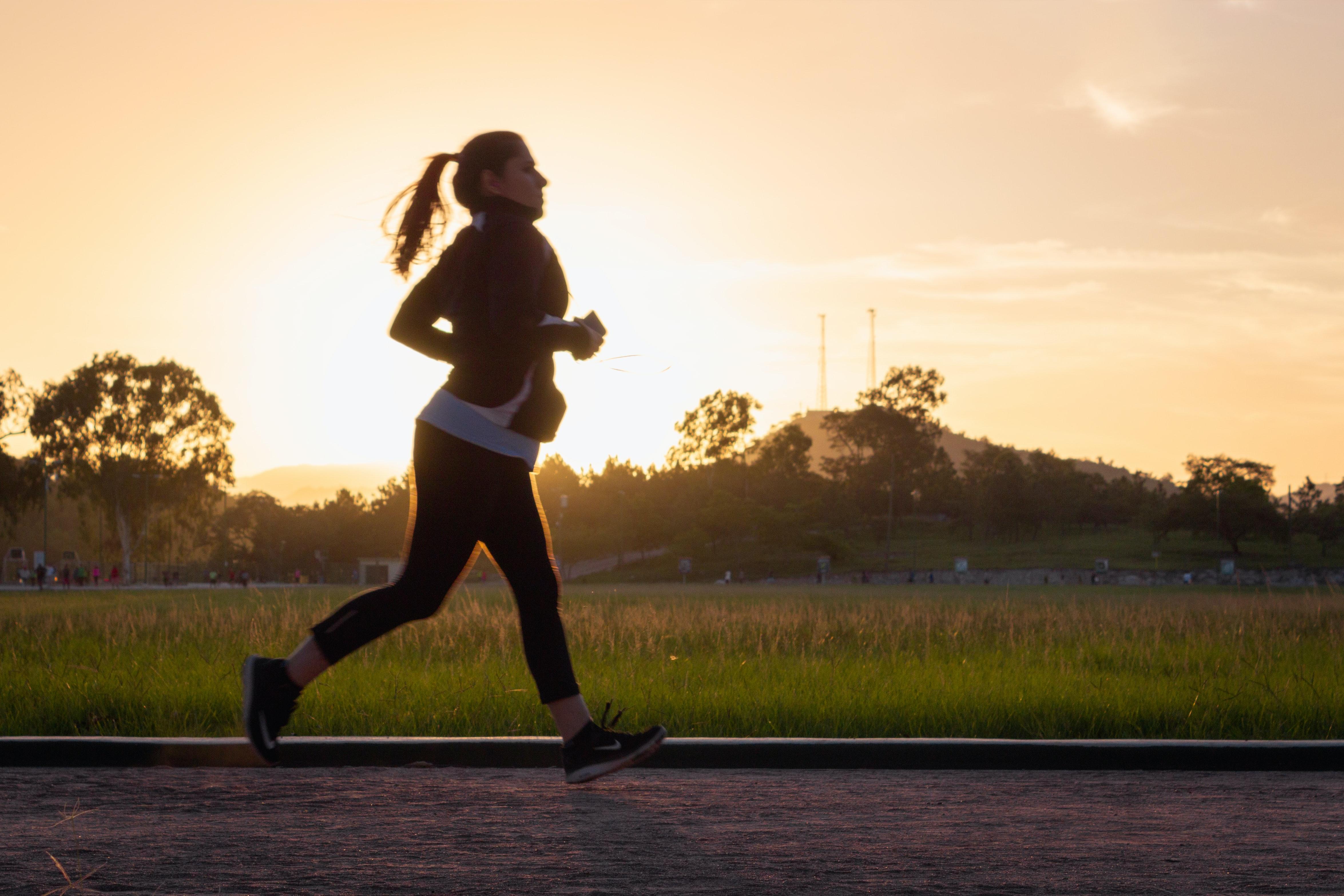 Woman running at sunset.