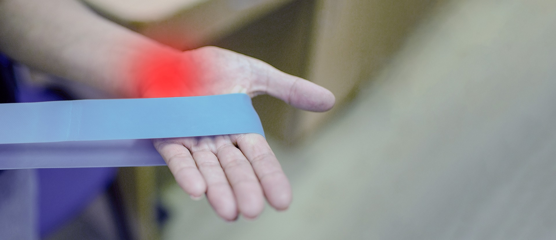 Elasting band around a hand and a red stained area to illustrate inflammation.