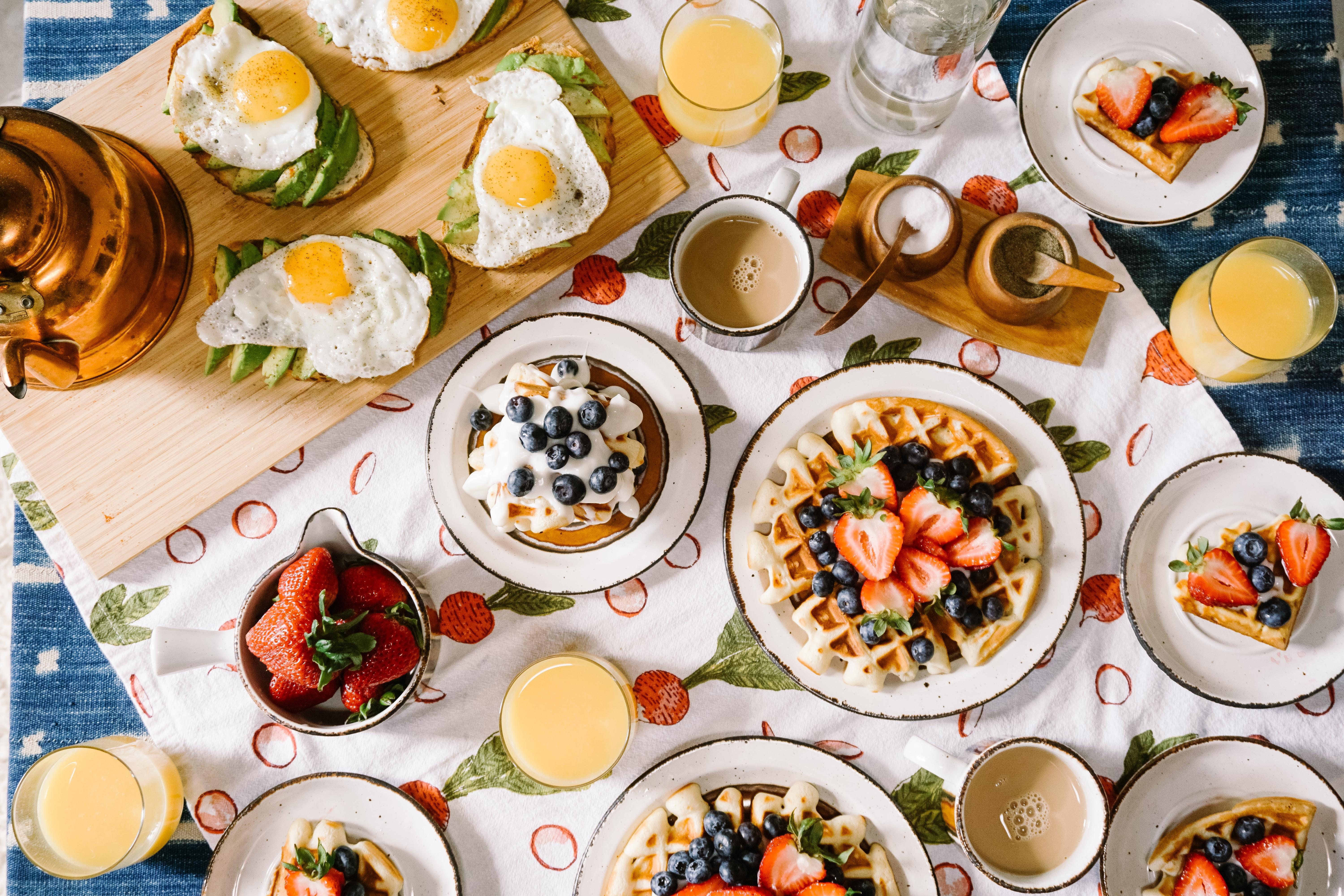 Waffels, fruits, coffee and fried eggs on small plates on a table.
