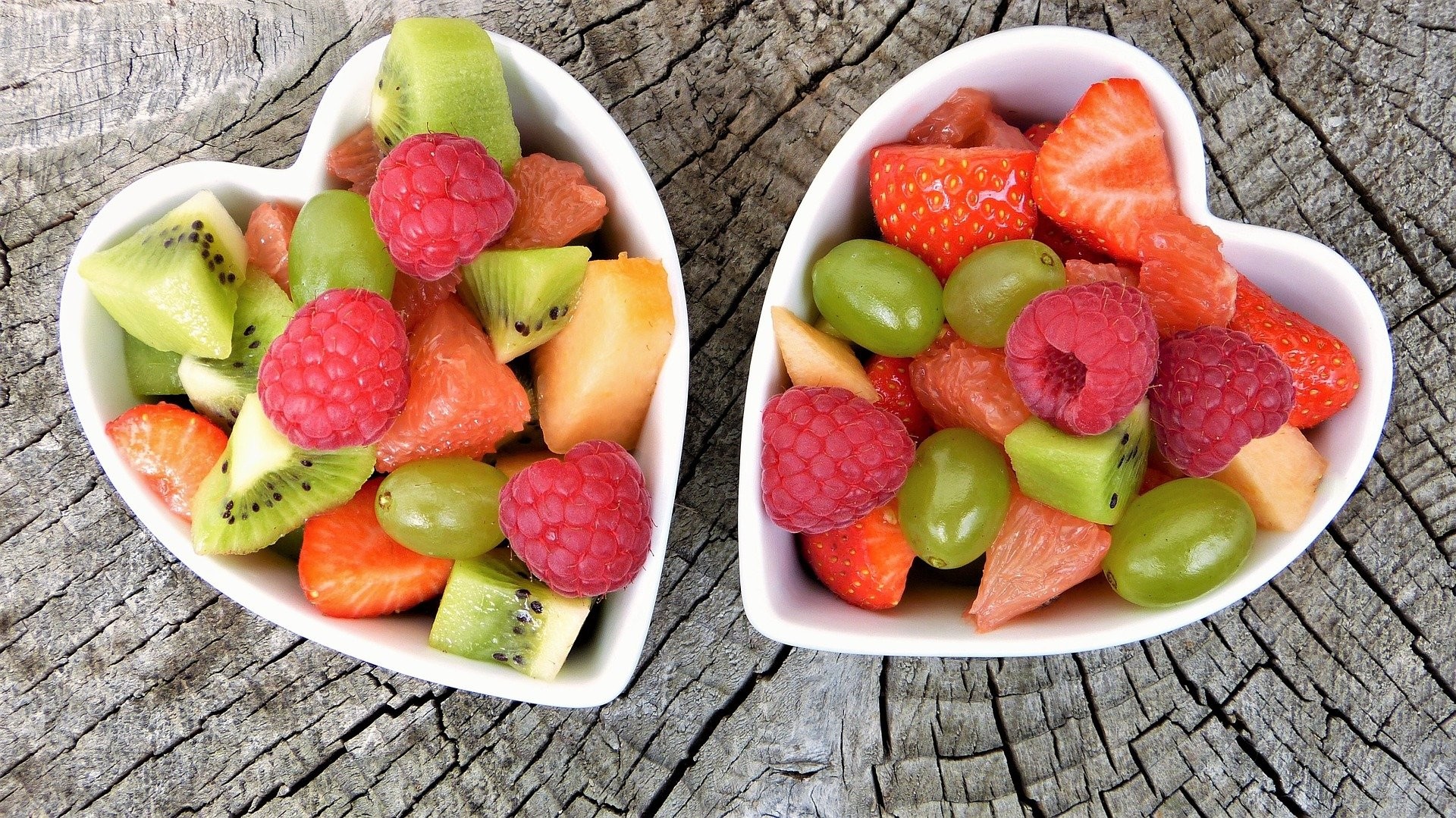 Two heart-shaped bowls with mixed fruits.