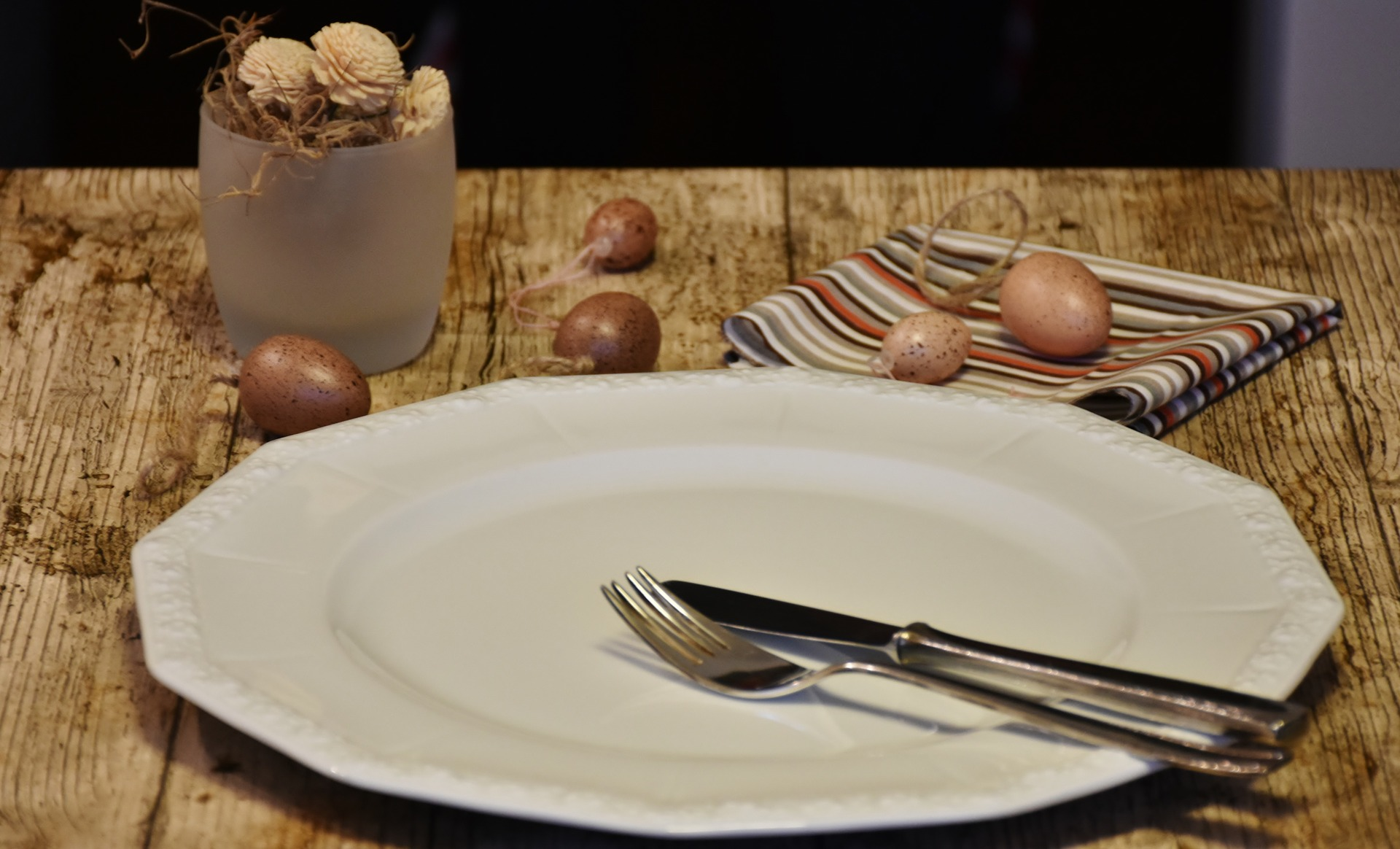 Empty plate and cutlery on a wooden table.