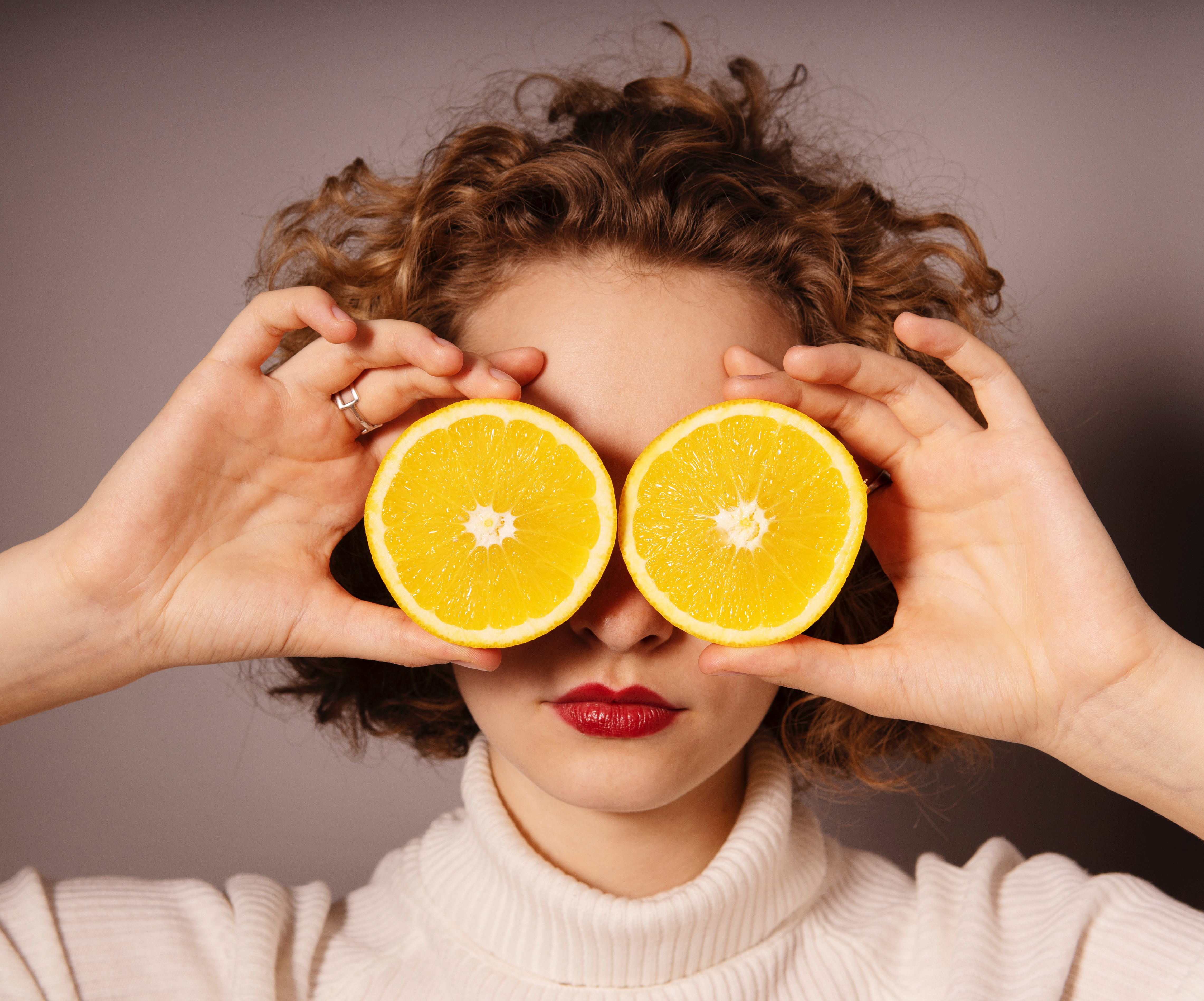 Woman with two half oranges in front of her eyes.